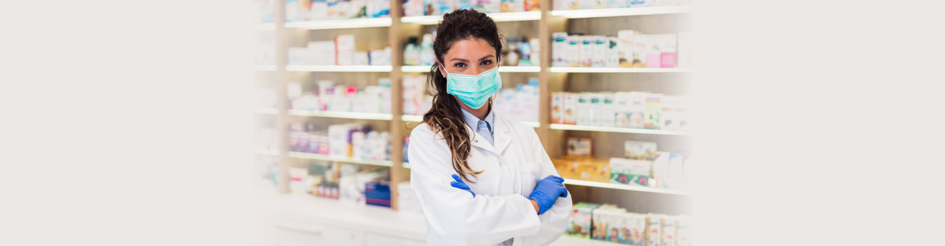 Female pharmacist with protective mask on her face working at pharmacy